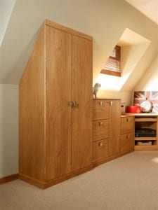 Fitted oak office wardrobe adjoining a sloping ceiling, showing space optimisation benefits of bespoke furniture