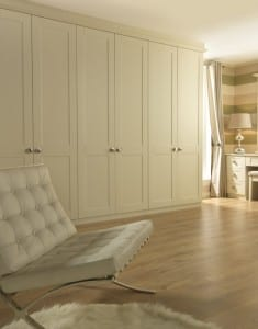 Chalk white run of fitted Shaker wardrobes with chair and rug in foreground