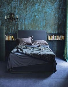 Moody inky blue bedroom with bed and bedside book cases