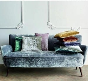 Grey velvet textured sofa with rich coloured cushions