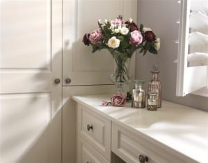 Fitted wardrobe stable door adjoining a matching dressing table in vintage-style cream