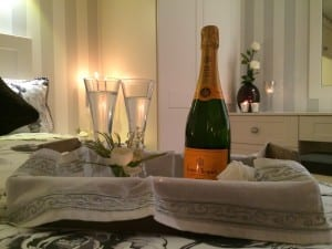 Valentines setting with a bottle of champagne resting on a bed against a backdrop of a cream shaker bedroom