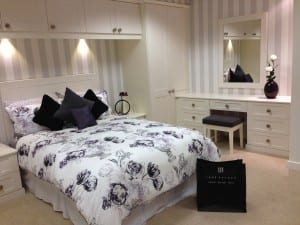 Fitted Shaker style bedroom showing bridging unit, stable door and dressing table with bold wall mirror & stool in cream