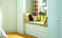 Classic fitted bedroom furniture focusing on the window area, with window seat, pelmet, drawers below & adjoining wardrobes